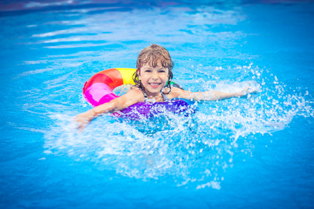 playing in the sea: Happy child playing in swimming pool. Summer vacation concept Stock Photo