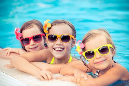 reir: Felices los niños en la piscina. Niños divertidos jugando al aire libre. Concepto de las vacaciones de verano