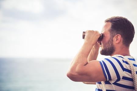 El hombre del marinero mirando a través de los prismáticos contra el cielo azul