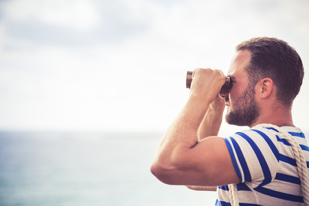 Sailor man looking through the binoculars against blue sky  Stock Photo