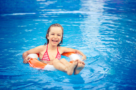 summer fun: Happy child playing in swimming pool. Summer vacation concept Stock Photo