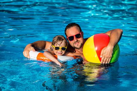 niños nadando: El niño feliz y padre jugando en la piscina. Concepto de las vacaciones de verano
