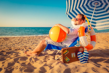 sunbed: Happy young man sitting on the beach. Summer vacation concept Stock Photo