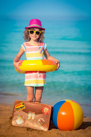 suitcase: Happy child with vintage suitcase on the beach. Summer vacation and travel concept