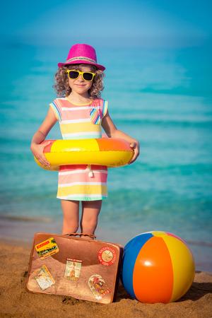 maleta: Niño feliz con la maleta de la vendimia en la playa. Las vacaciones de verano y el concepto de viaje