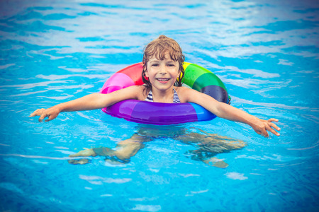 Happy child playing in swimming pool. Summer vacation concept Stock fotó