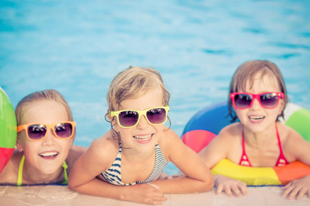 baby swimming: Happy children in the swimming pool. Funny kids playing outdoors. Summer vacation concept