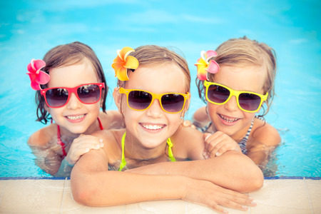 pool water: Happy children in the swimming pool. Funny kids playing outdoors. Summer vacation concept