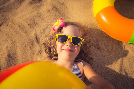 Happy child lying on the sand. Funny kid holding beach ball. Unusual top view portrait
