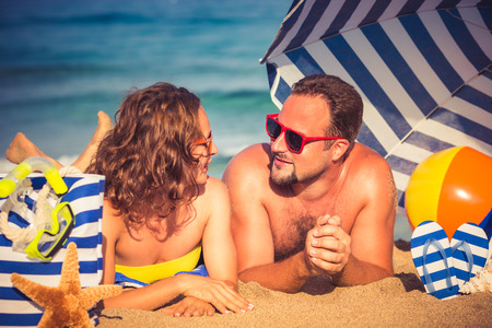 happy couple: Happy couple in love. People lying on the beach. Young man and woman talking outdoors. Summer vacation concept Stock Photo