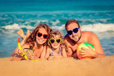 lazer: Família feliz que joga na praia. Conceito de férias de verão