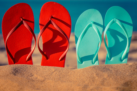 flipflops: Two pair flip-flops on the sand. Summer vacation concept Stock Photo