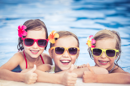 niños nadando: Niños felices que muestran los pulgares para arriba en la piscina. Niños divertidos jugando al aire libre. Concepto de las vacaciones de verano