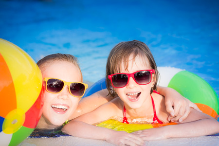 sunglass: Happy children in the swimming pool. Funny kids playing outdoors. Summer vacation concept