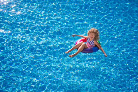 Happy child playing in swimming pool. Summer vacation concept. Top view portrait Stock fotó