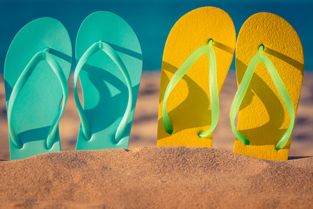 Two pair flip-flops on the sand. Summer vacation concept Banco de Imagens