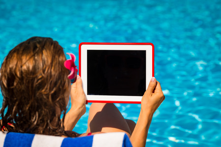 Woman holding tablet PC with black blank screen against blue water background. Summer vacation concept photo