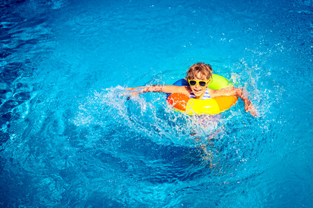 niños nadando: Niño feliz que juega en la piscina. Concepto de vacaciones de verano. Vista superior retrato