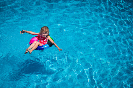 splash pool: Happy child playing in swimming pool. Summer vacation concept. Top view portrait Stock Photo