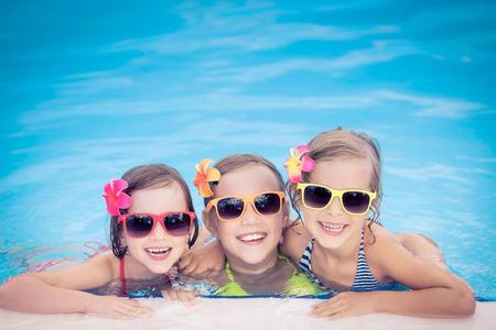 スイミング プールで幸せな子供たち。面白い子供たちが野外で遊ぶ。夏の休暇の概念