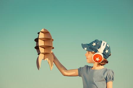 pilotos aviadores: Ni�o feliz que juega con el cohete de juguete contra el fondo del cielo de verano. Retro tonificado Foto de archivo