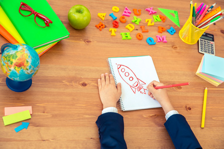 person writing: Child writing in copybook. School items on wooden desk in class. Education concept. Top view Stock Photo