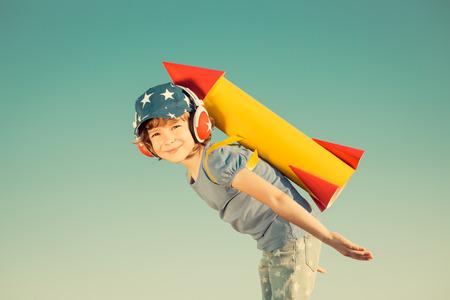 aventura: Niño feliz que juega con el cohete de juguete contra el fondo del cielo de verano. Retro tonificado Foto de archivo