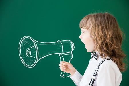 lideres: Cabrito de la escuela en la clase. Niño feliz contra la pizarra verde. Concepto de la educación Foto de archivo