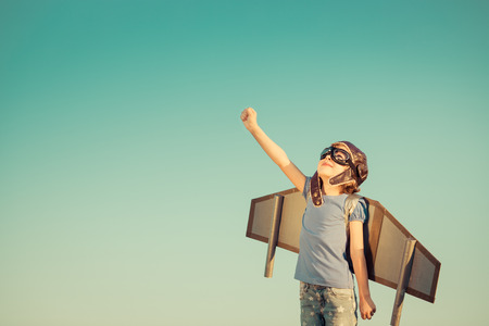 Úspěch: Šťastné dítě hrát s hračkou křídly proti letní oblohy pozadí. Retro tónovaný