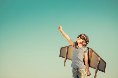 gente exitosa: Niño feliz que juega con las alas de juguete contra el fondo del cielo de verano. Retro tonificado