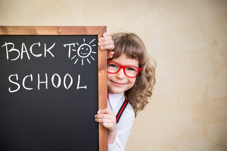 School kid in class. Happy child holding blackboard blank. Education concept 스톡 콘텐츠