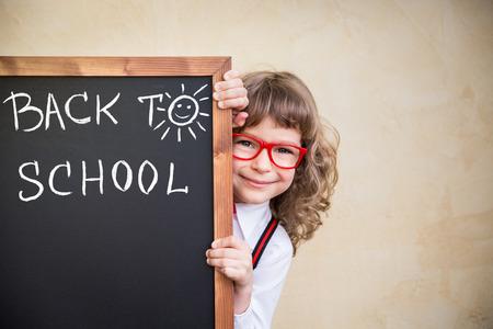 scuola: Kid scuola in classe. Bambino felice che tiene lavagna vuota. Concetto di formazione