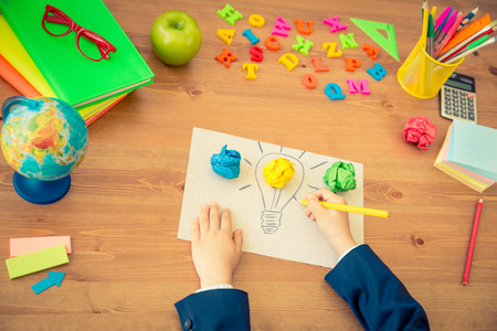 Child drawing lamp bulb on paper. School items on wooden desk in class. New bright idea concept. Top view