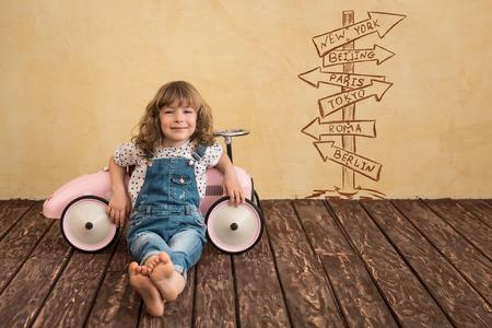 soñar carro: Niño feliz que juega en casa. Viaje del coche. Las vacaciones de verano y el concepto de viaje Foto de archivo