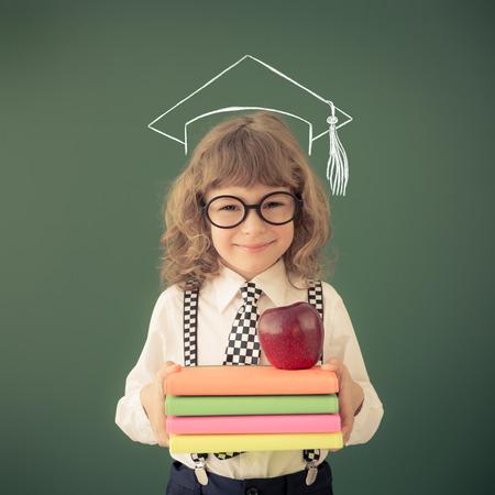 education: School kid in class. Happy child against green blackboard. Education concept