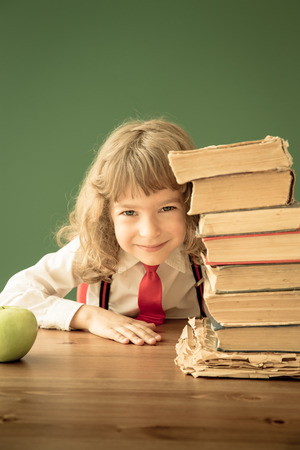 School kid sitting at desk in class. Happy child against green blackboard. Education concept photo