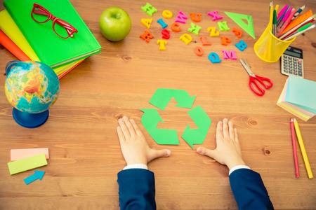 niños reciclando: Niño que sostiene el símbolo de reciclaje en las manos. Cole en escritorio de madera en clase. Concepto de la educación. Vista superior