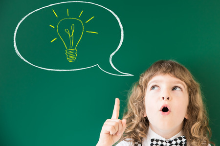 blackboard: Cabrito de la escuela en la clase. Niño feliz contra la pizarra verde. Concepto de la educación Foto de archivo