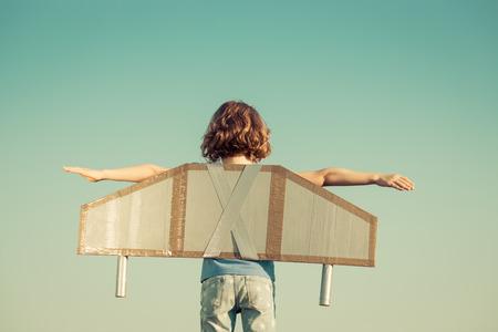 Счастливый ребенок играет с игрушечными крыльями против летом фоне неба. Ретро тонированное