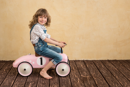 Happy child playing at home. Car trip. Summer vacation and travel concept