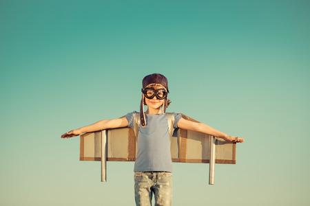 lider: Niño feliz que juega con las alas de juguete contra el fondo del cielo de verano. Retro tonificado