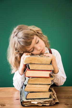 niños estudiando: Cabrito de la escuela sentado en el escritorio en la clase. Niño feliz contra la pizarra verde. Concepto de la educación Foto de archivo