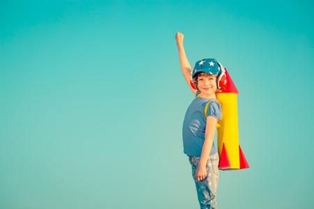 juguetes: Ni�o feliz que juega con el cohete de juguete contra el cielo de verano de fondo