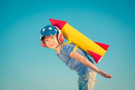 여름 하늘 배경에 장난감 로켓을 가지고 노는 행복한 아이
