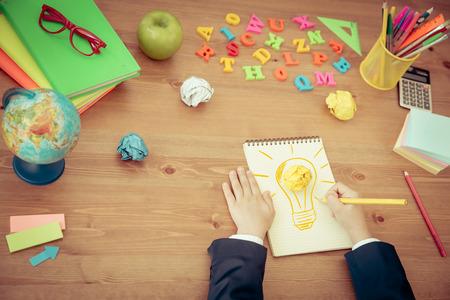 niño escuela: Niño dibujo bombilla de la lámpara en cuaderno. Cole en escritorio de madera en clase. Nuevo concepto de idea brillante. Vista superior Foto de archivo