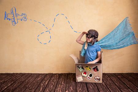 Счастливый ребенок играет в картонной коробке. Малыш весело дома