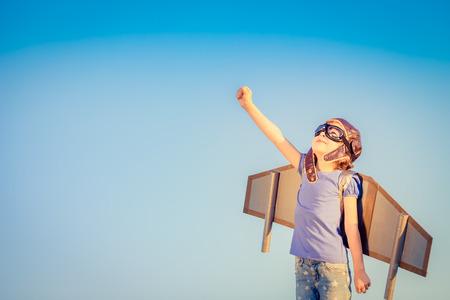pilotos aviadores: Niño feliz que juega con las alas de juguete contra el cielo de verano de fondo Foto de archivo