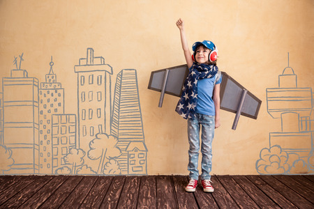 idea: Happy child playing at home. Kid having fun with toy paper wings Stock Photo
