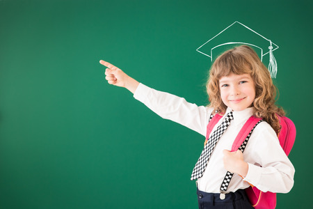 School kid in class. Happy child against green blackboard. Education concept