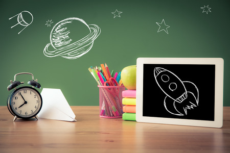 Tablet PC in classroom against green blackboard. Education concept Stock Photo